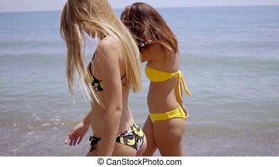 Two young women walking away along a beach