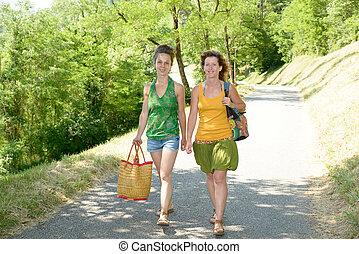 two young women walking by the lake