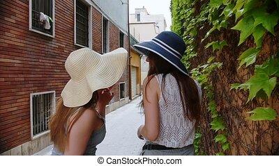 Two young women walking in panamas. Mid shot