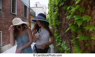 Two young women walking in panamas on the streets along a...