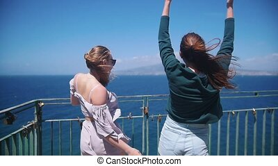Two young women walking on an observation deck. Looking at...
