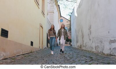 Two young women walking on the narrow streets. Mid shot