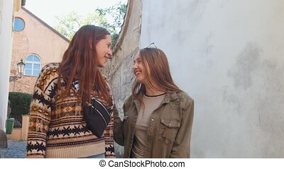 Two young women walking on the narrow streets. Talking and...