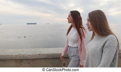 Two young women walking on the quay. Mid shot