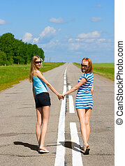 Two young women walking on the road countryside