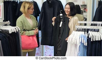 Two young women walking through the mall. Woman shopping....