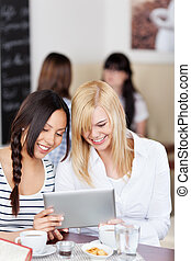 young women watching tablet-pc in cafe