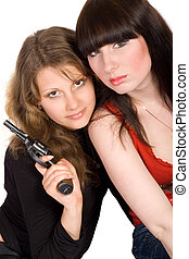 Two young women with a pistol. Isolated