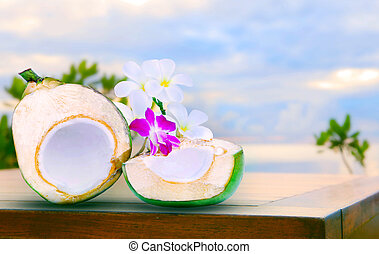 twon half of green coconut water on top  wood table with tropica