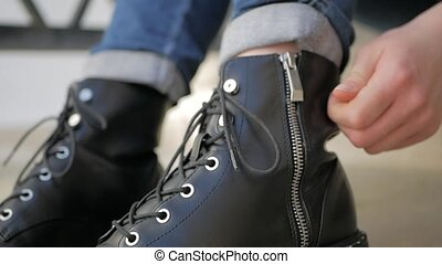 Tying black leather Shoes boots by zipper.