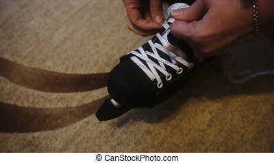 tying the white laces on skates,preparing to go on the ice.
