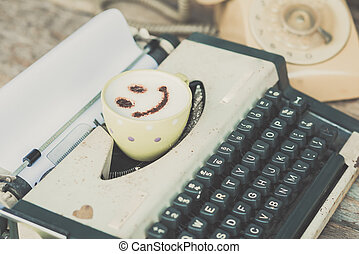 Typewriter with coffee cup and retro phone, sepia tone.