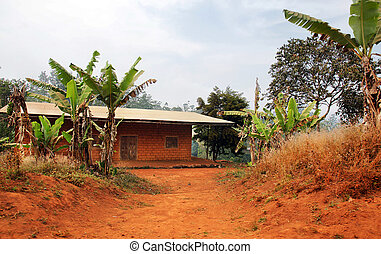 Typical African red clay or soil brick with tin roof house