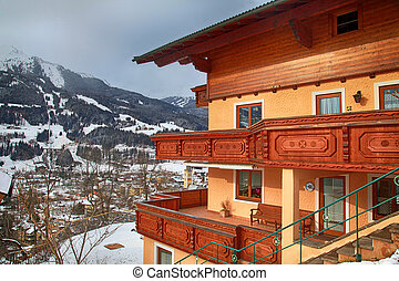 alpin house with wooden balcony in winter mountain village, Alps, Austria.