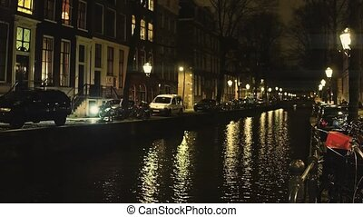 Typical Amsterdam canal and houses alongside embankment at...