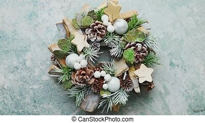 Typical beautiful Christmas wreath made with pines, wooden ornaments and leafs. Top view, flat lay