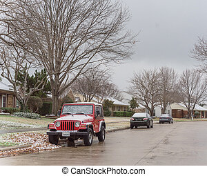 Typical bungalow house and parked cars under winter snow cover near Dallas