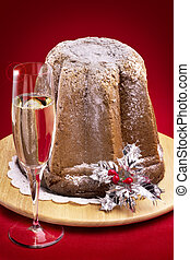 typical christmas cake with sparkling wine on red background