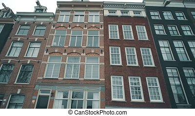 Typical Dutch houses facades along the street in Amsterdam,...