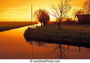 Typical dutch landscape in the countryside from the Netherlands at sunset