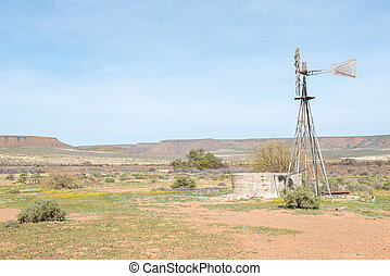 Typical farm scene with water pumping windmill and dam