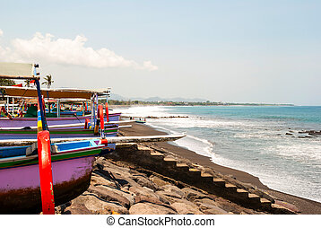 Typical indoneisan boats called jukung on the beach of...