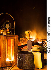 Piece of typical seasoned cheese from Pienza, Italy in front of a country fireplace.