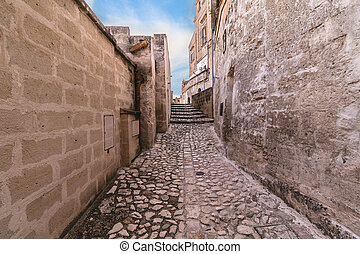 typical old street and stairs view of Matera under blue sky