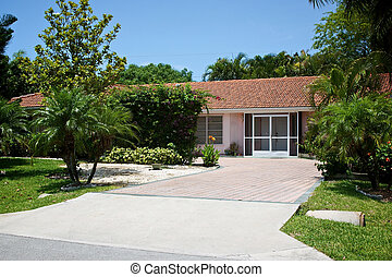 Pretty view of an average one level home in south west florida, surrounded by tropical trees and plants.