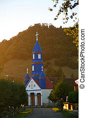 Typical painted wooden church on Chiloe island, Patagonia, Chile at twilight