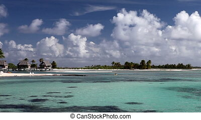 Typical Polynesian landscape - island with palm trees and small houses on water in the ocean