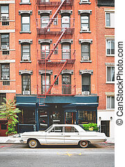 Typical red brick buildings with fire stairs in NYC. Classic car in the foreground and vintage photo effect.