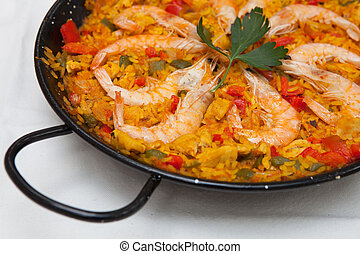 typical spanish paella, with seafood and vegetables, in a paellera