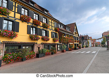 Empty street in Alsace with yellow half-timbered house with flowers