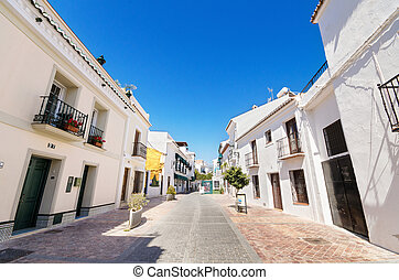 Typical street with white houses in the touristic village of Nerja, Malaga, Spain.