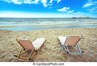 Typical summer image of an amazing pictorial view of a sandy beach with an old white church in a small island at the background, Malia, Crete, Greece.