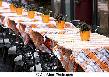 typical tables laid with checkered tablecloth for a stylish Italian restaurant