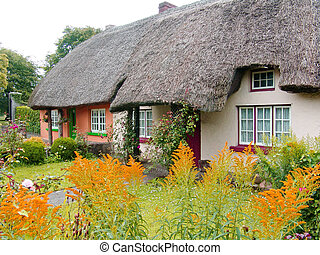 Typical thatched roof cottage in Ireland, with a garden in the front.