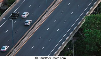 Cars move continuously at a steady pace, along an elevated section of highway in Asia. Video 4k
