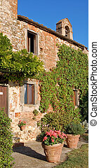 Typical Tuscan Farmhouse with ivy and vases of flowers