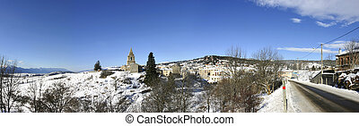 Typical village and church under the snow in the mountains ...