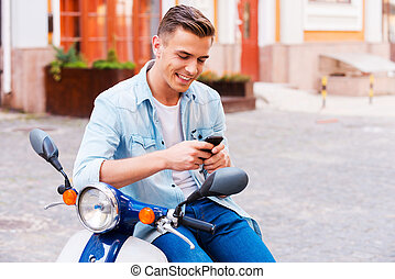 Typing a message to friend. Cheerful young man sitting on scooter and looking at his mobile