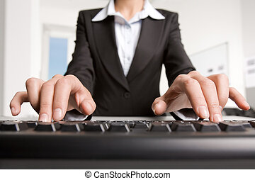 Typing - Close-up of businesswoman in black suit typing a...