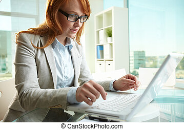 Typing in office - Pretty business lady working on laptop in...