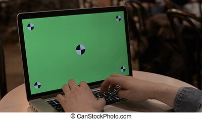 typing on a laptop with green screen
