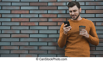 Typing text message. Side view of handsome young man in smart casual wear holding mobile phone while leaning at the brick wall with coffee.