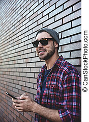 Typing text message. Side view of handsome young man in smart casual wear holding mobile phone while leaning at the brick wall.