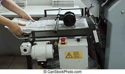 Typography - polygraph printing process - a female's hand completes a paper for a newspaper