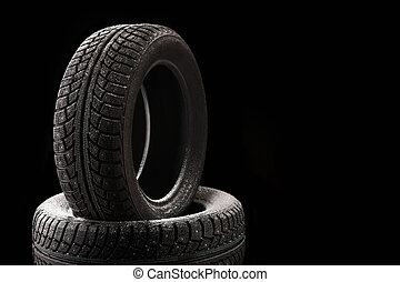 Snow-covered winter tyre covers, isolated on a black background