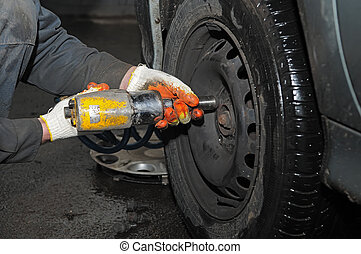 tyre fitting repair with air compressed wrench - two hands...
